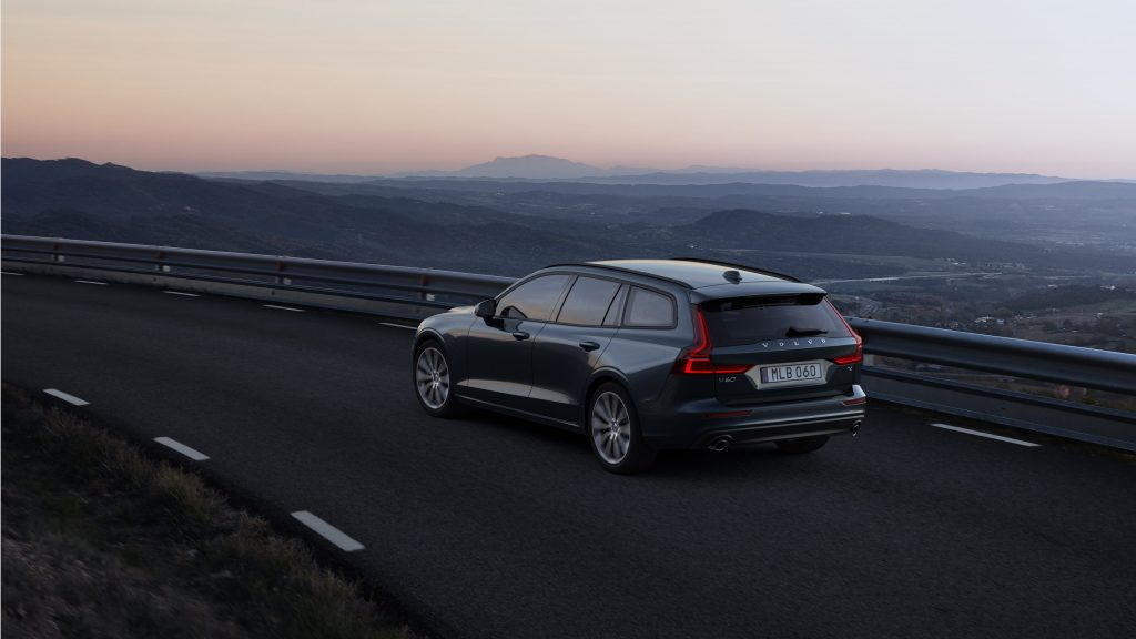 A dark blue Volvo V60 on a mountain road at sunset, photographed from the rear