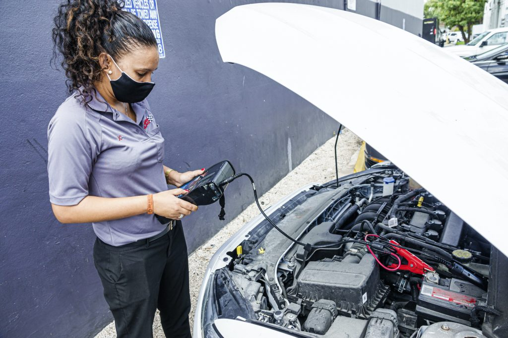 An Advance Auto Parts employee tests a car battery.