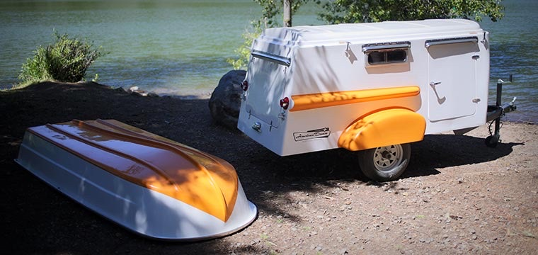 The American Dream in sherbert orange by a lake with the roof boat off