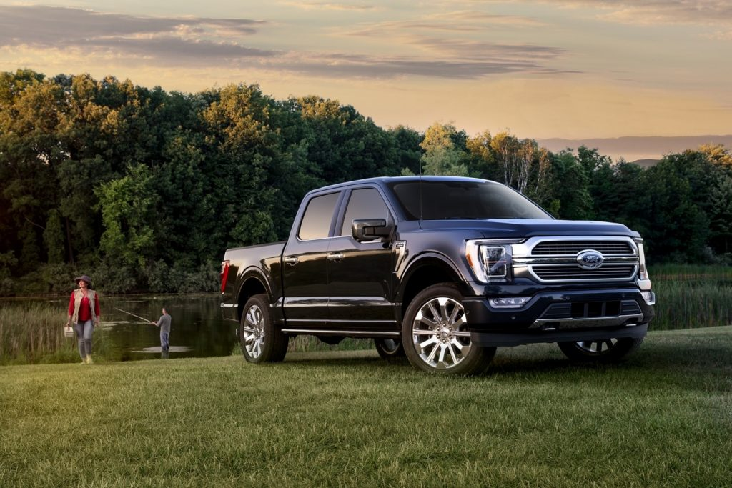 A navy blue 2021 Ford F150 in front of a lake while a man fishes and a woman carries a tackle box.