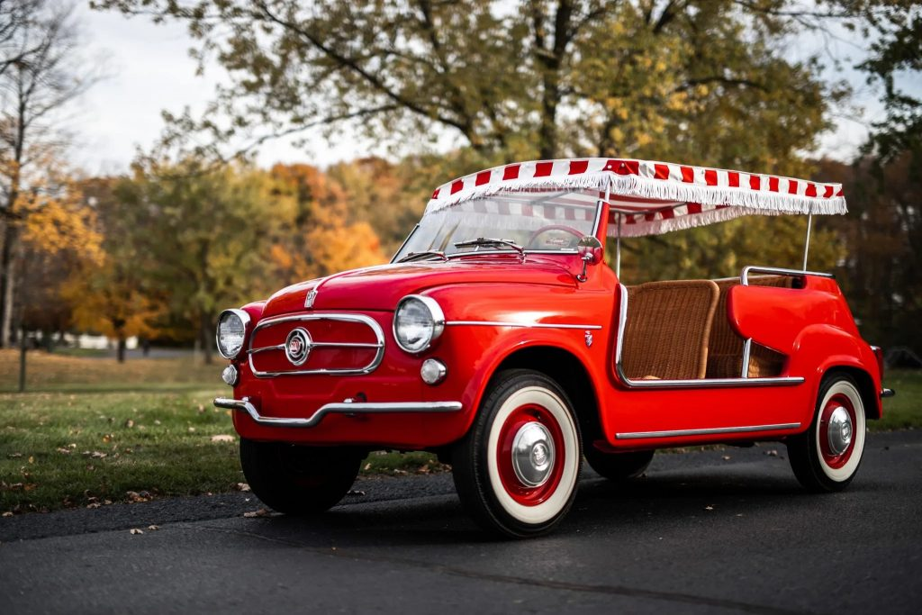 A red 1958 Fiat Jolly 600 parked on a driveway