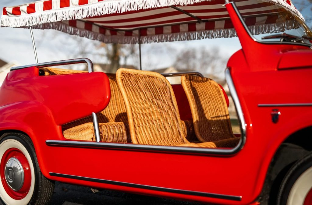 A side view of the wicker interior of a red 1958 Fiat Jolly 600