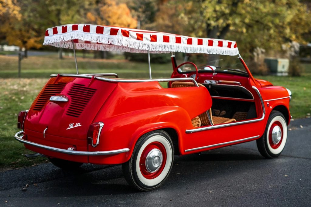 The rear 3/4 view of a red 1958 Fiat Jolly 600 parked on a driveway