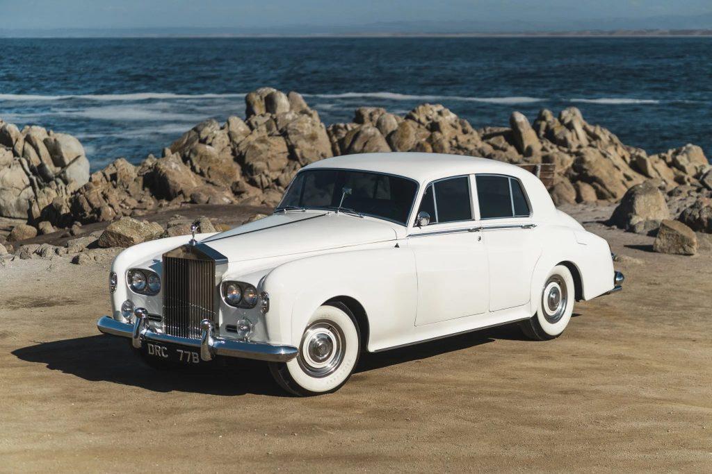 A white 1965 Rolls-Royce Silver Cloud III on a rocky beach by the ocean