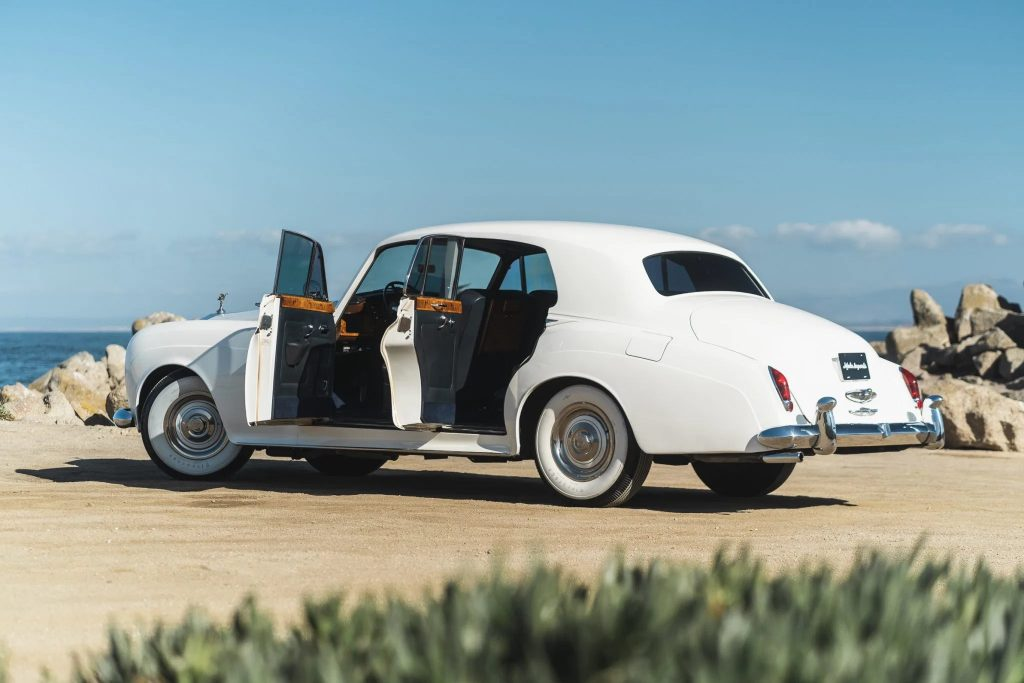 The rear 3/4 view of a white 1965 Rolls-Royce Silver Cloud III with its doors open on a beach