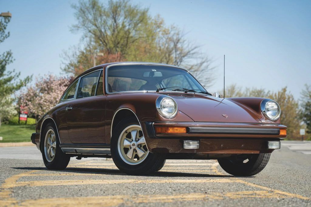 The front 3/4 view of a brown 1975 Porsche 911 S in a parking lot