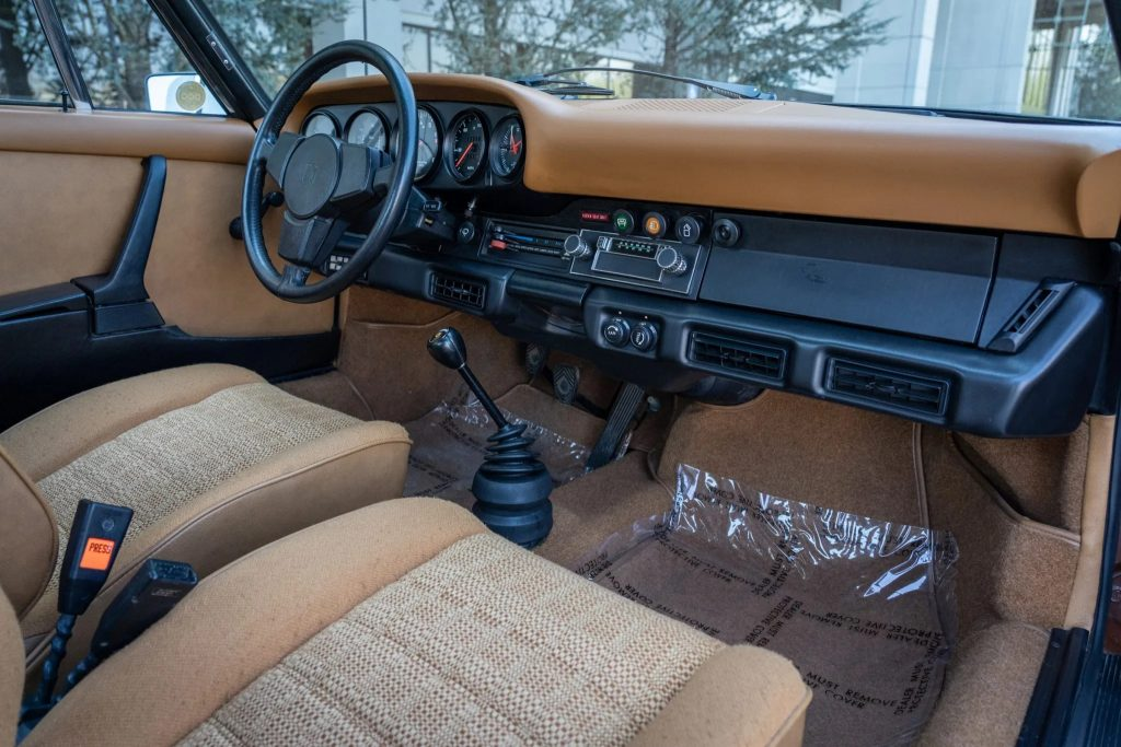 The tan-cloth front seats and black-and-tan dashboard of a 1975 Porsche 911 S