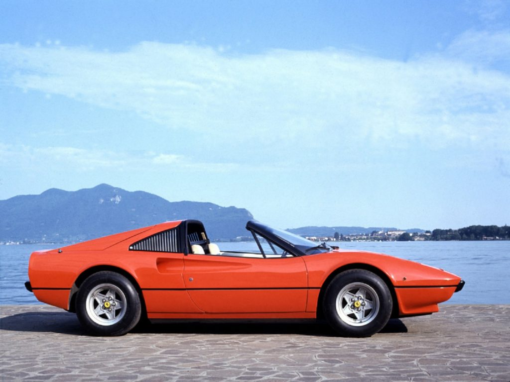 The side view of a red 1977 Ferrari 308 GTS with its roof off parked next to a lake