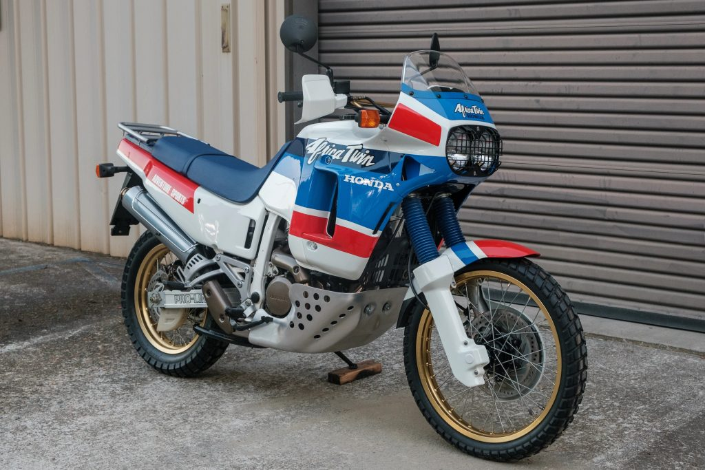 A white-blue-and-red RD03-gen 1989 Honda XRV650 Africa Twin by a gray building