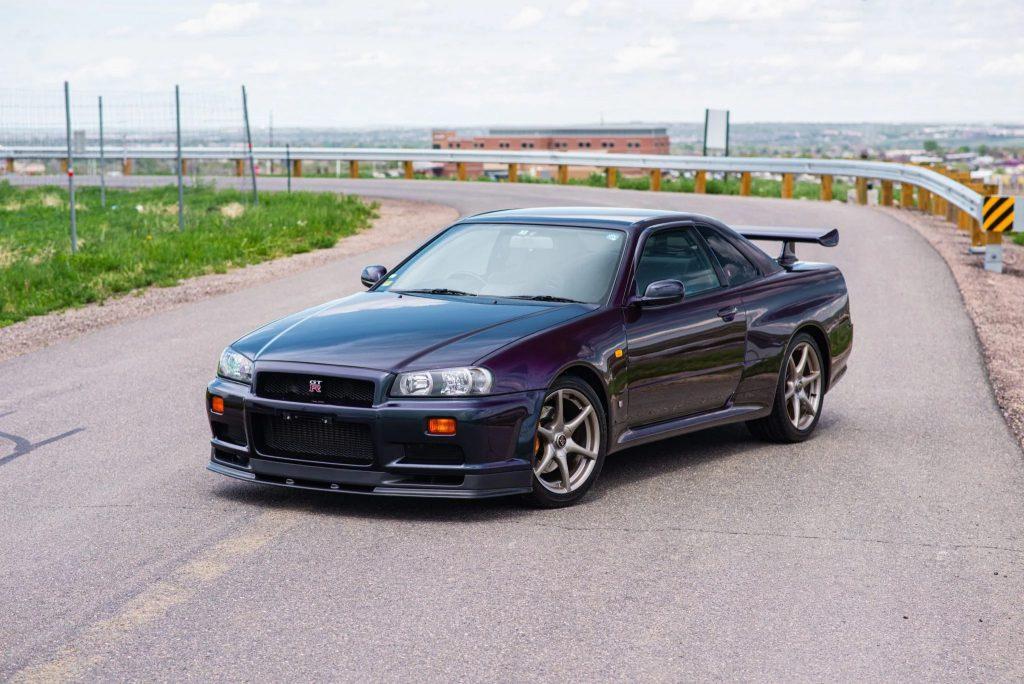 A Midnight Purple II 1999 R34 Nissan Skyline GT-R V-Spec on a road