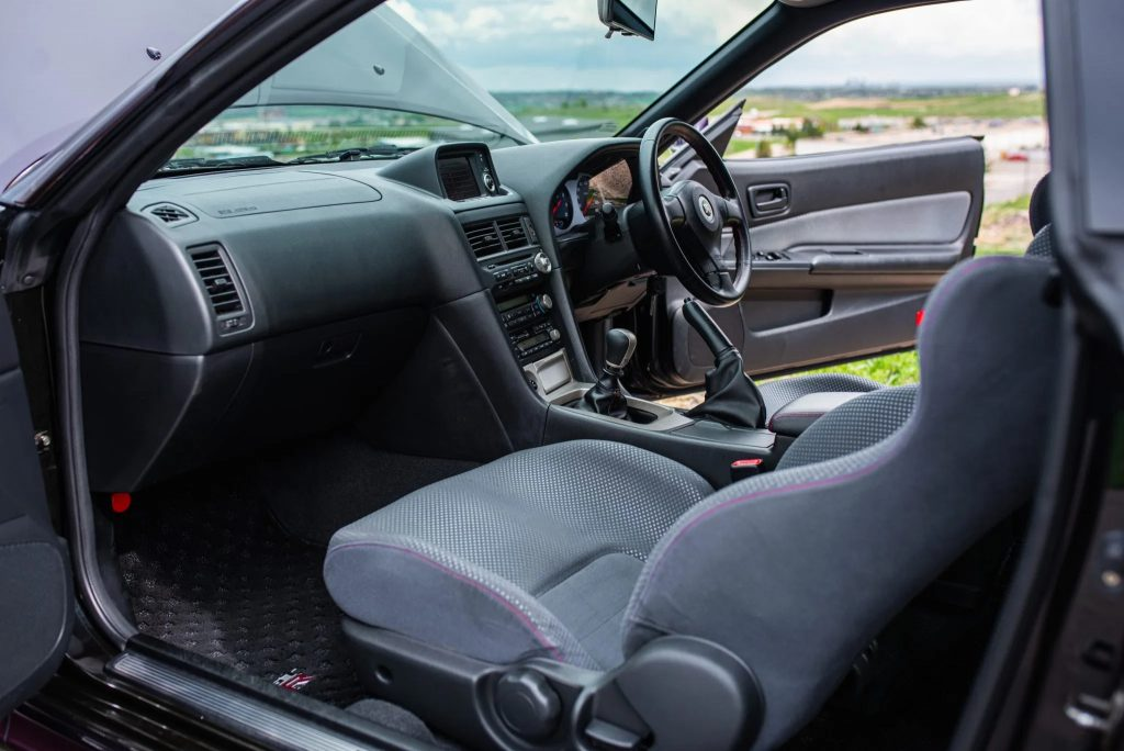 The gray front seats and dashboard of a 1999 R34 Nissan Skyline GT-R V-Spec seen through the open doors