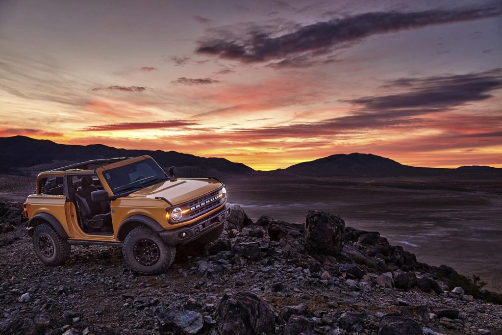 A yellow Ford Bronco off road at sunset