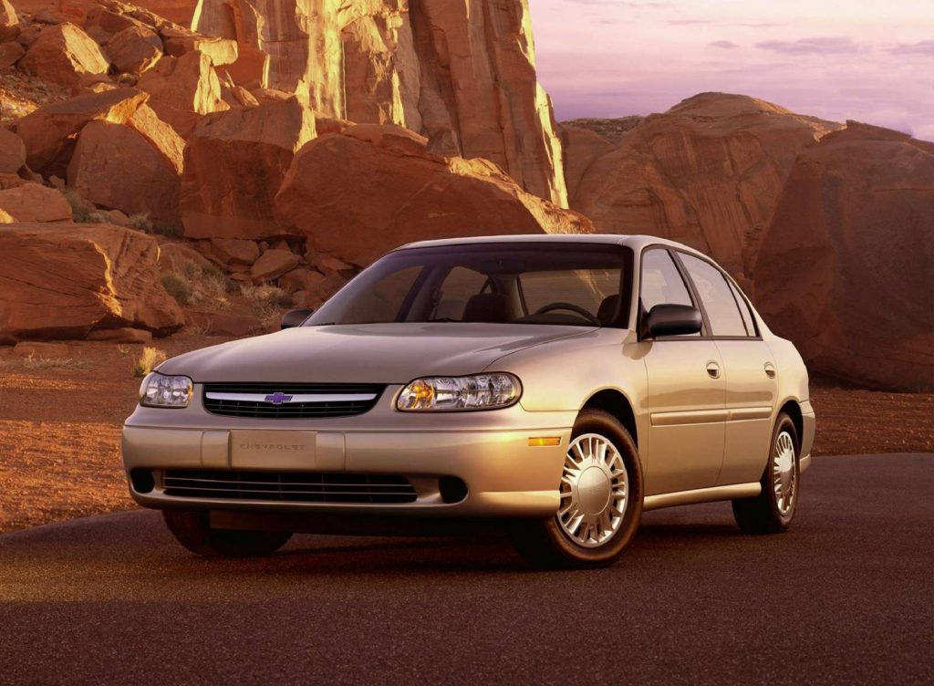 A tan 2002 Chevrolet Malibu amongst desert rocks