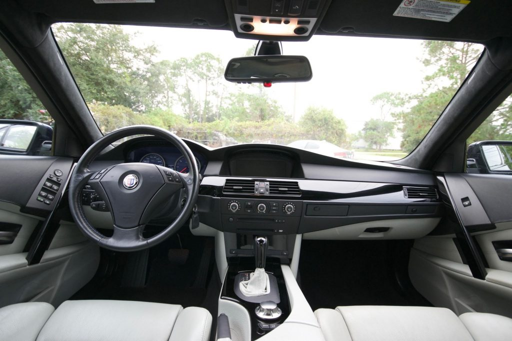 The white-leather front seats and black dashboard of a 2005 BMW Alpina B5