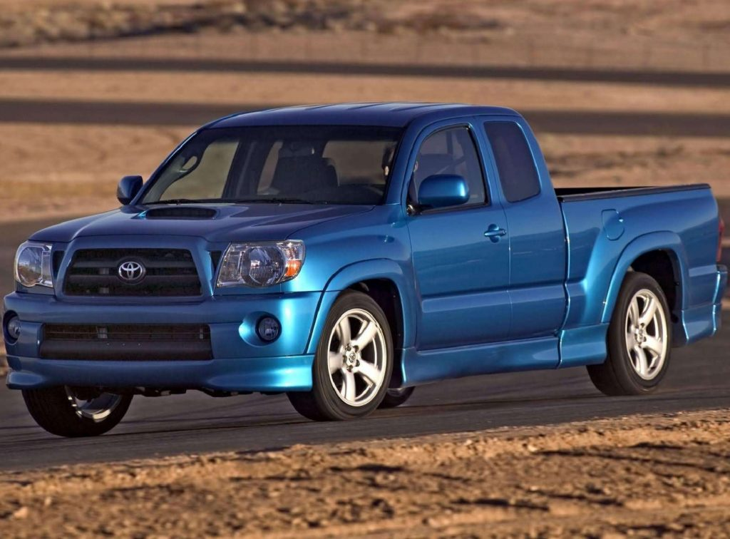 A blue 2005 Toyota Tacoma X-Runner goes around a corner of a desert racetrack