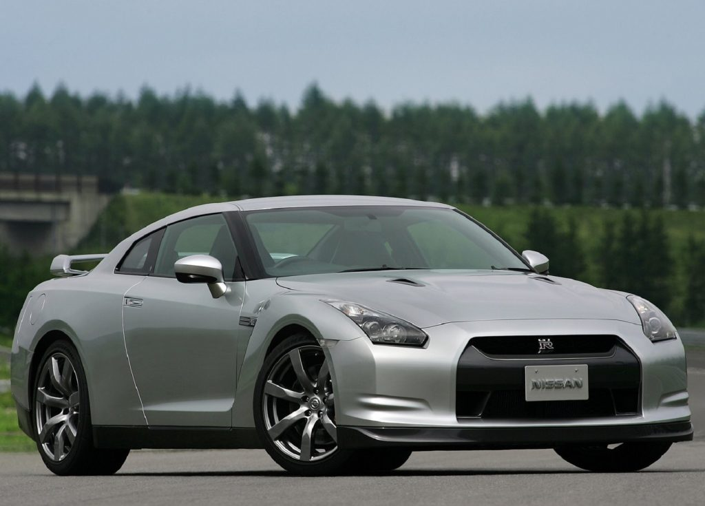 A silver 2009 Nissan GT-R on a track next to a forest