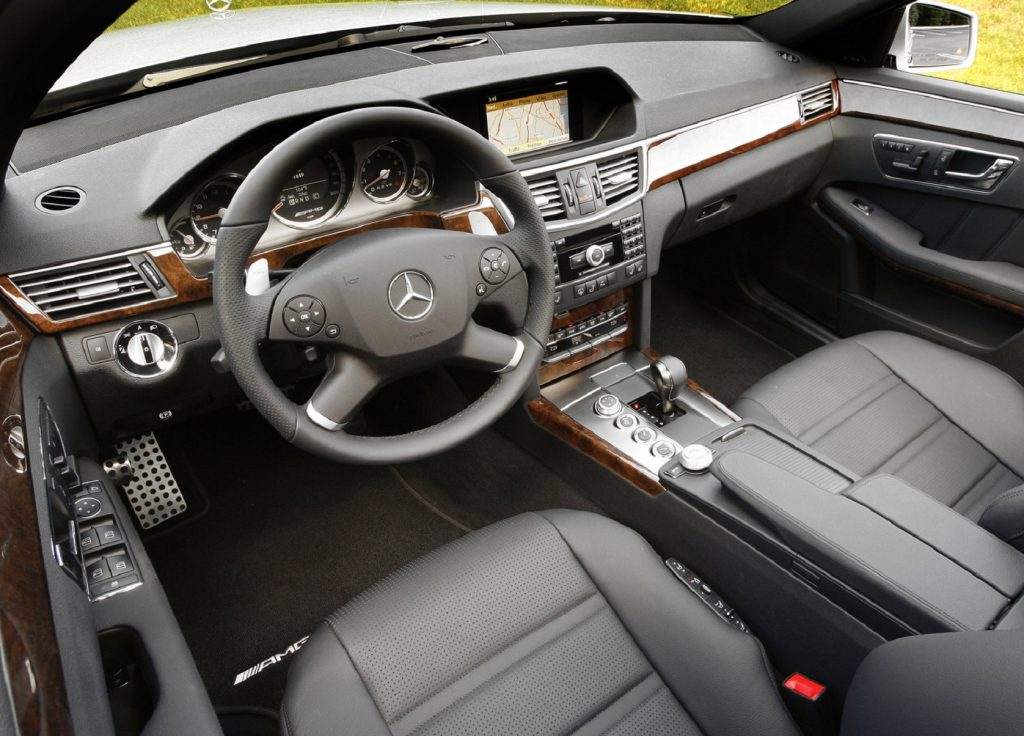 The black-leather front seats and wood-and-leather-trimmed dashboard of a 2010 Mercedes-Benz E63 AMG
