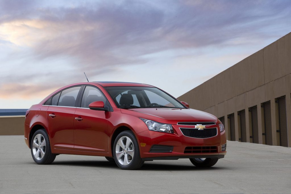 A red 2011 Chevrolet Cruze parked on a roof with a blue sky and wispy clouds in the background