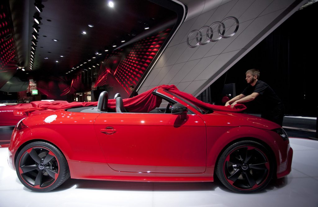 An employee unfurls the protective cover of an Audi AG TT automobile displayed on the company's stand ahead of the opening day of the Paris Motor Show in Paris, France, on Wednesday, Sept. 26, 2012.