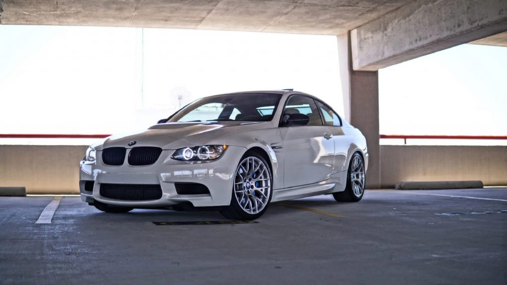 A white 2012 BMW M3 Competition Coupe in a parking garage