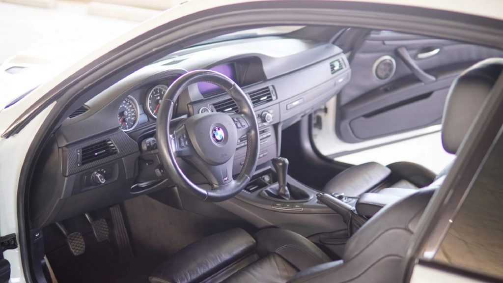 The black-leather-upholstered front seats and carbon-fiber-trimmed dashboard of a 2012 BMW M3 Competition Coupe seen through the open doors
