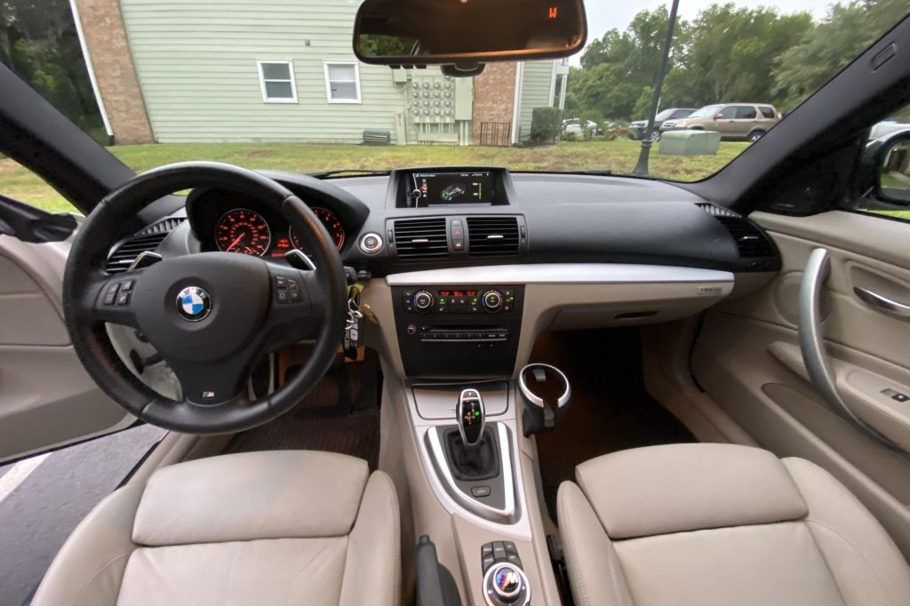 The tan-leather front seats and black dashboard of a 2013 BMW 135is Coupe