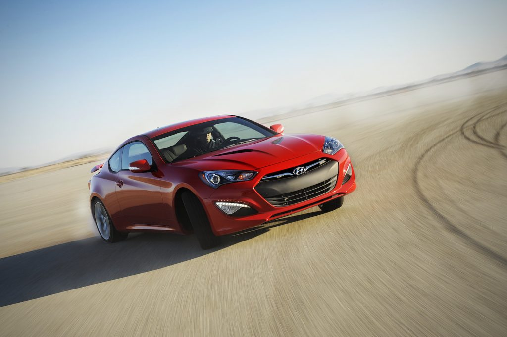 A red 2014 Hyundai Genesis Coupe driving, the 2014 Hyundai Genesis Coupe is one of the fastest used cars under $15,000
