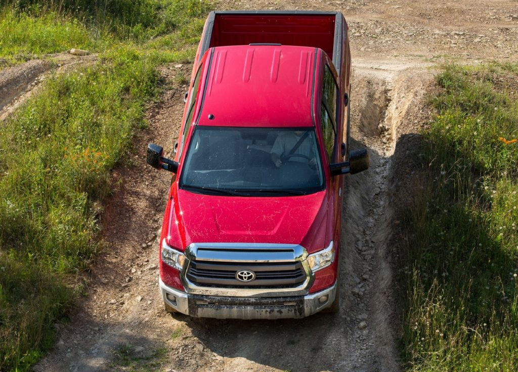 A red 2014 Toyota Tundra descents down a gravel path on a grassy hill