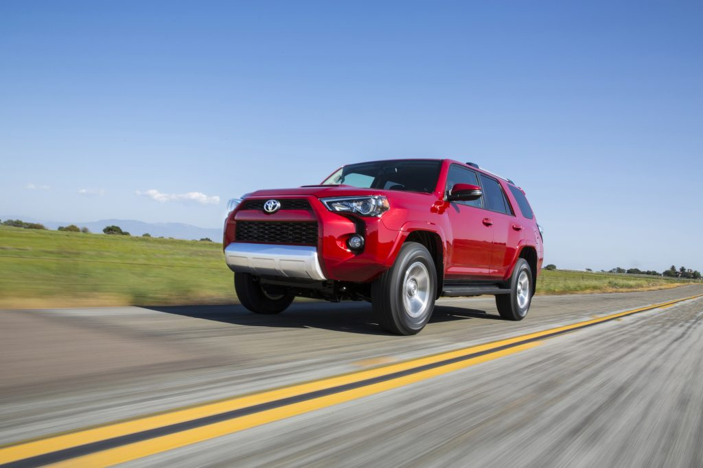 A red 5th Gen 4Runner rolling down a straight, empty road