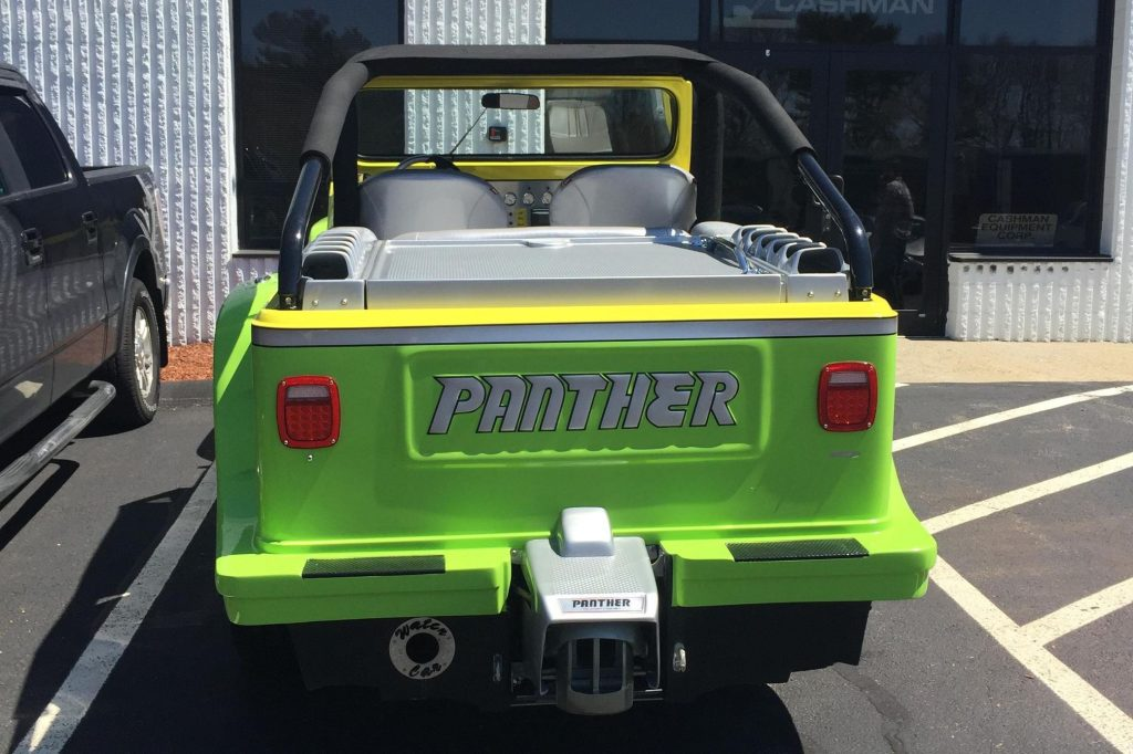 The rear view of a green-gray-and-yellow 2016 WaterCar Panther in a parking lot next to a black car