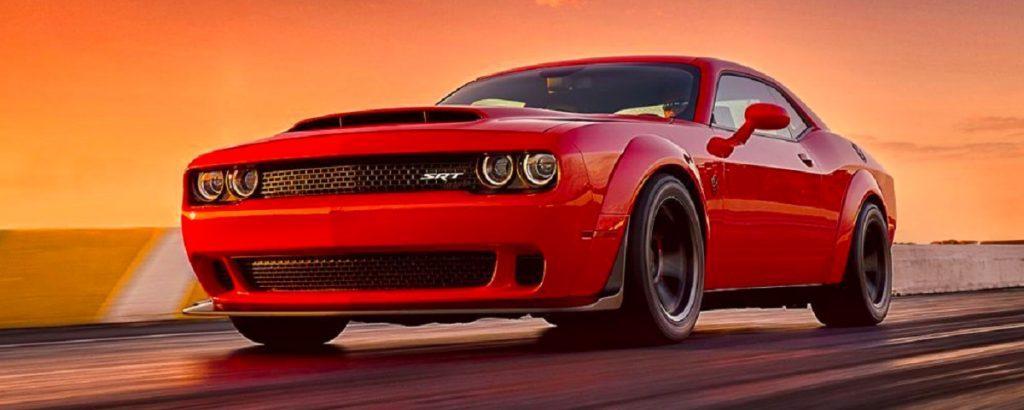 A red 2018 Dodge Challenger Demon against an orange setting sun.