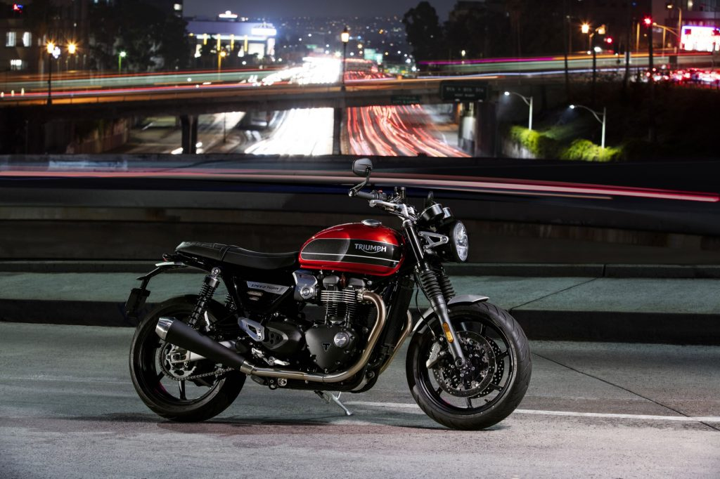 The side view of a red-and-black 2019 Triumph Speed Twin on a bridge over a highway at night