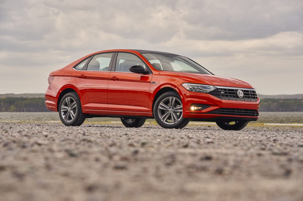 A red 2019 Volkswagen Jetta compact sedan parked on gravel on a cloudy day with mountains in the distance
