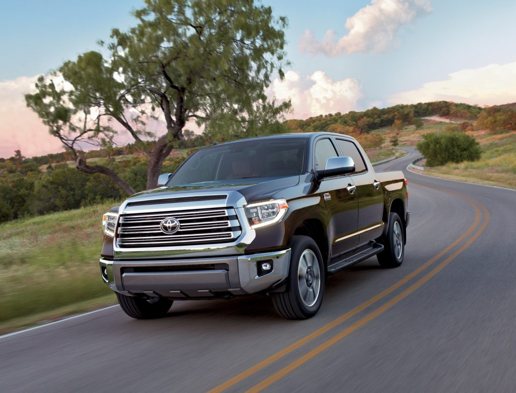 A brown Toyota Tundra rolls down a country road