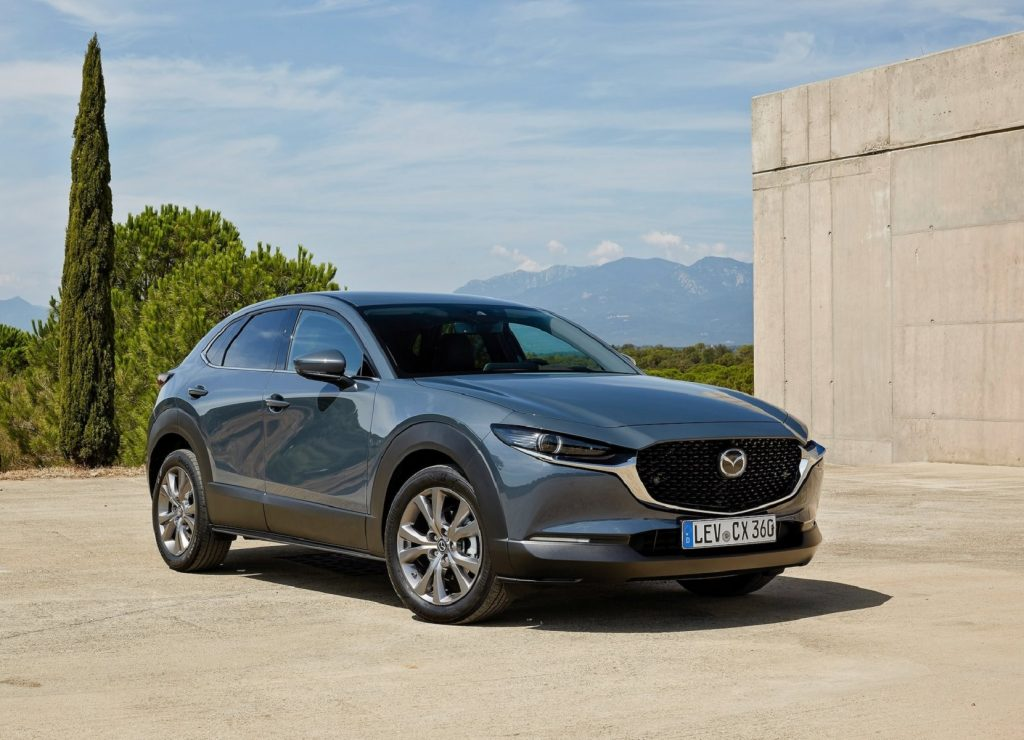 A silver-gray 2020 Mazda CX-30 by a building overlooking tree-covered mountains and hills