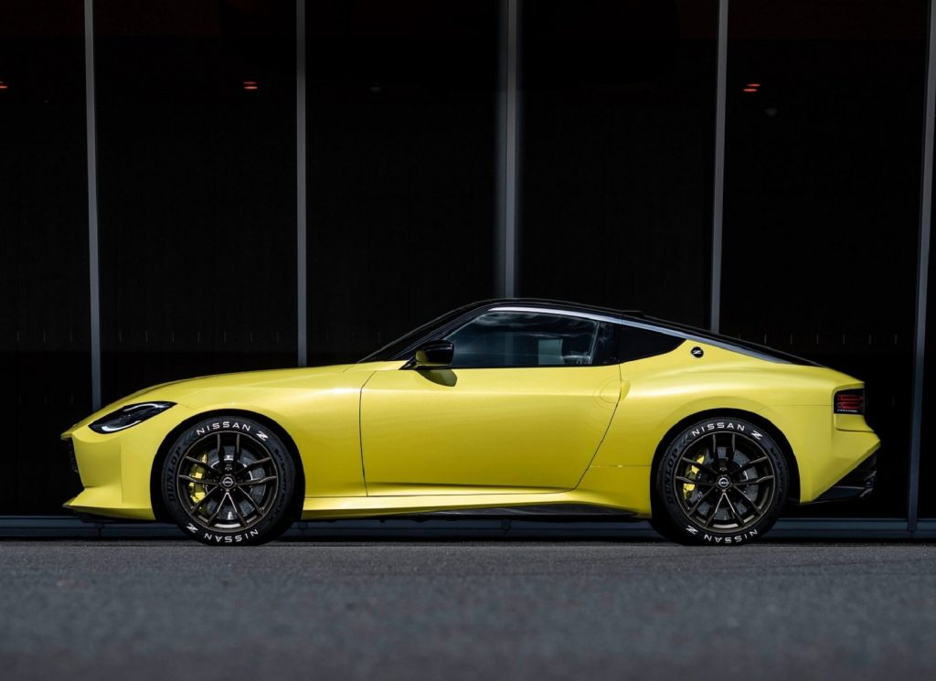 The side view of the yellow 2020 Nissan Z Proto Concept in front of a black building