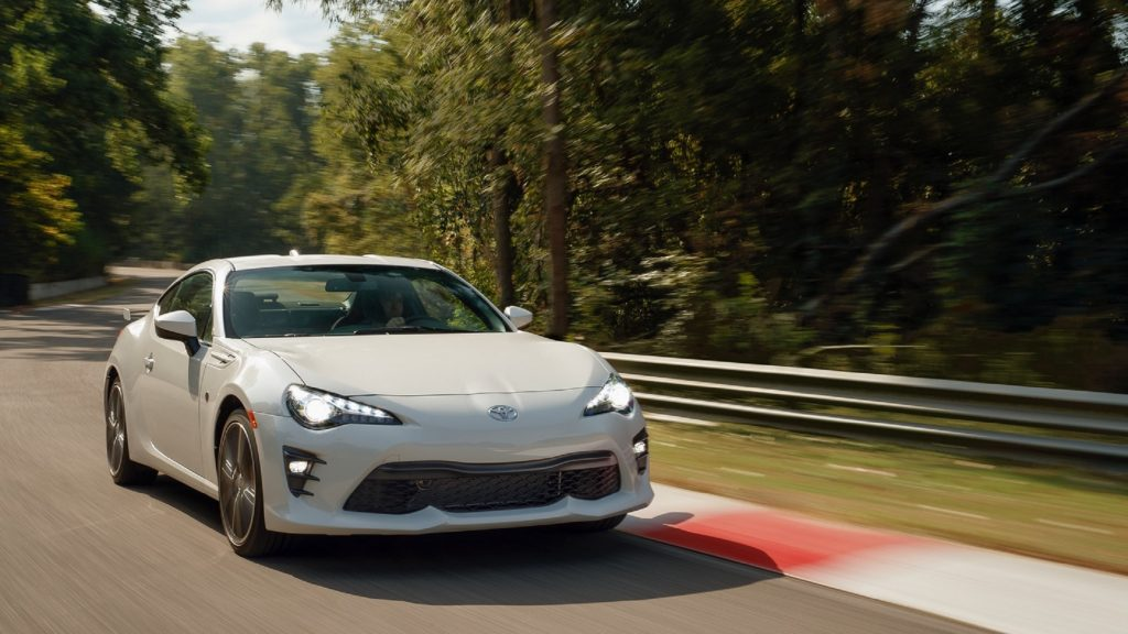 A white 2020 Toyota 86 GT with TRD Handling Package goes around a forested racetrack