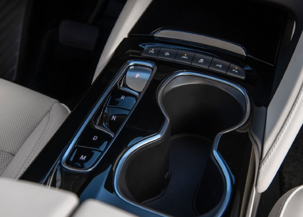 The black center console of a 2021 Buick Envision with the start-stop system deactivation button in the corner
