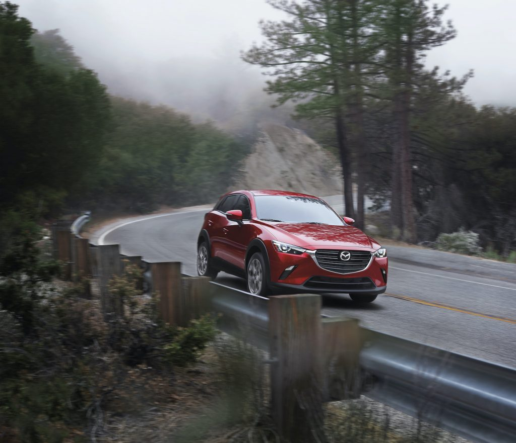 A red 2021 Mazda CX-3 driving, one of the most reliable new cars under $30,000