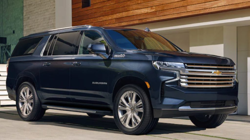 A blue 2021 Chevrolet Suburban SUV parked outside of a luxurious home.