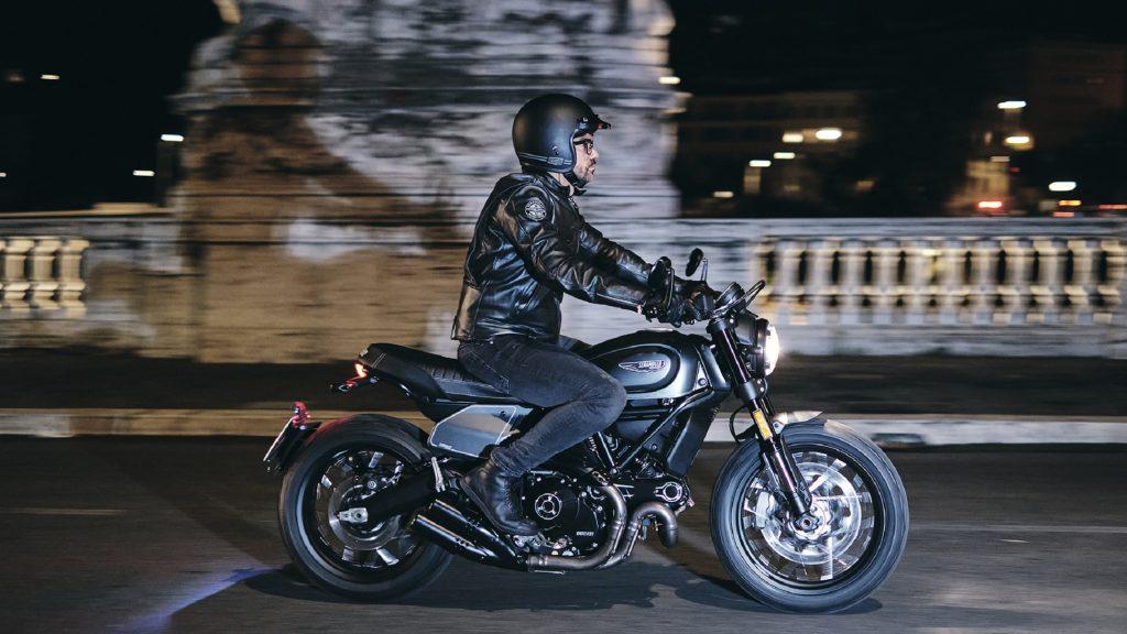 A black-clad rider on a gray-and-black 2021 Ducati Scrambler Nightshift riding through a city at night