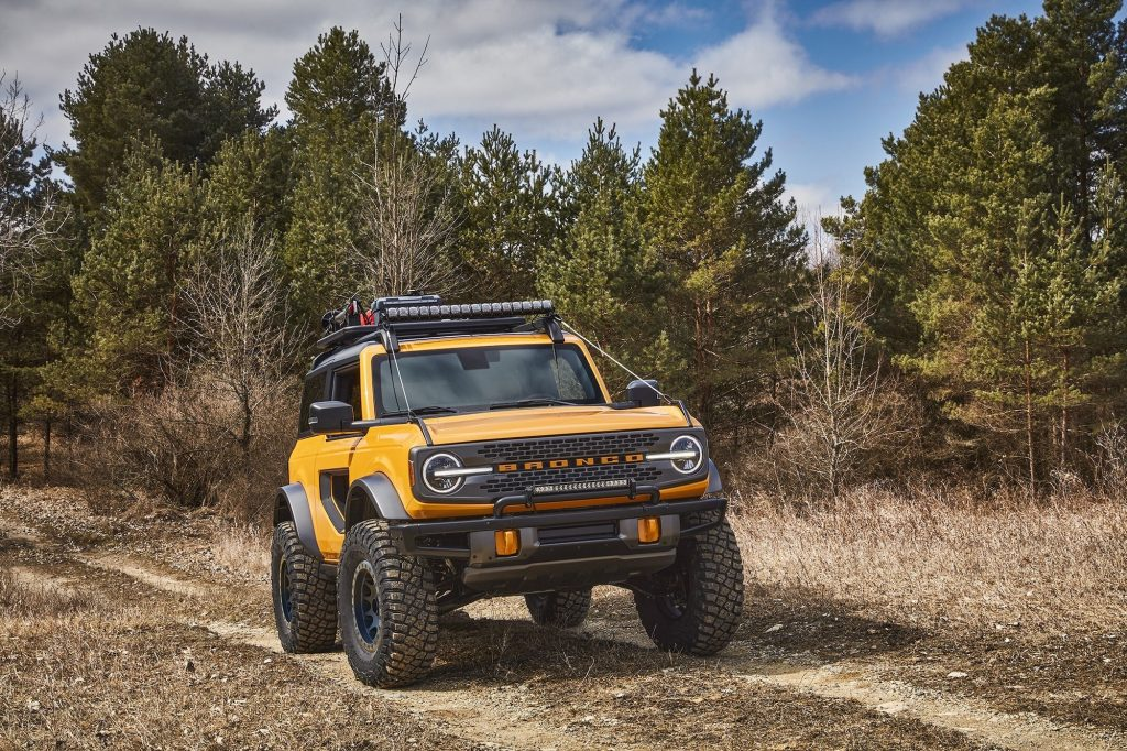 A yellow 2021 Ford Bronco compact SUV traveling on trail near a wooded area