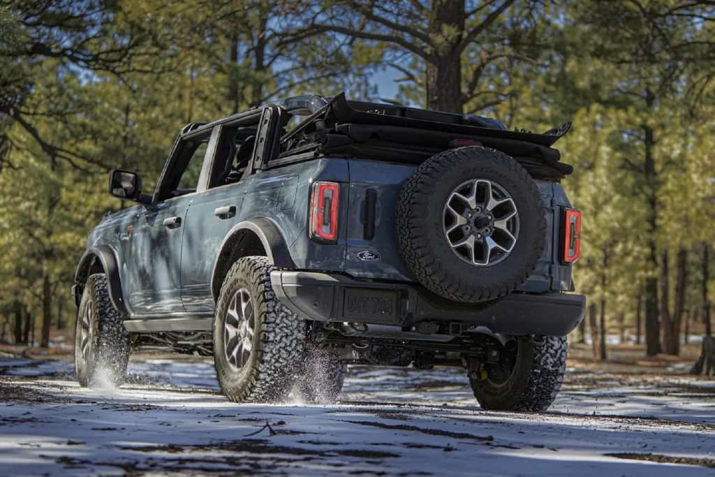 The rear 3/4 view of a bluish-gray 2021 Ford Bronco 4-Door Badlands with its roof down in a snowy forest