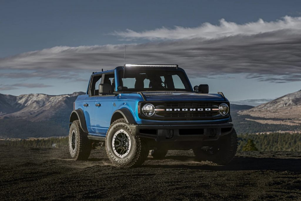 A blue 2021 Ford Bronco 4-Door Black Diamond with Sasquatch Package and light bar on a rocky mountain