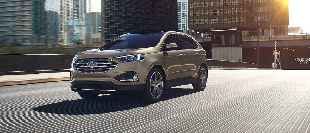 A gold 2021 Ford Edge travels over a bridge.