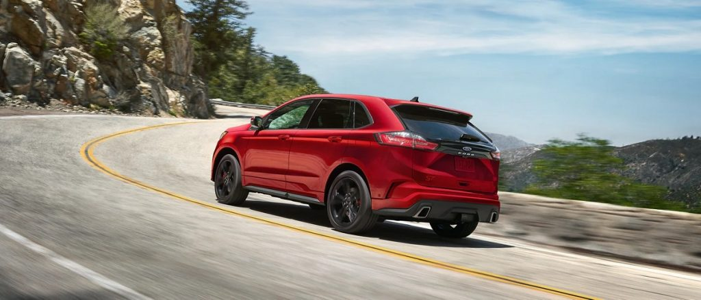 A red 2021 Ford Edge races down the highway.