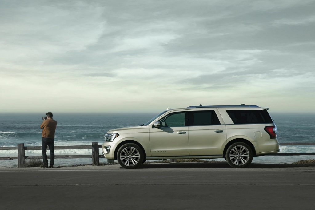 A beige 2021 Ford Expedition parked at the beach while a man takes pictures of the ocean.