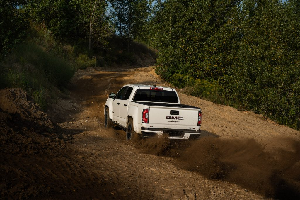 A white 2021 GMC Canyon AT4 Off-Road Performance Edition midsize pickup kicks up dirt as it travels up a hill