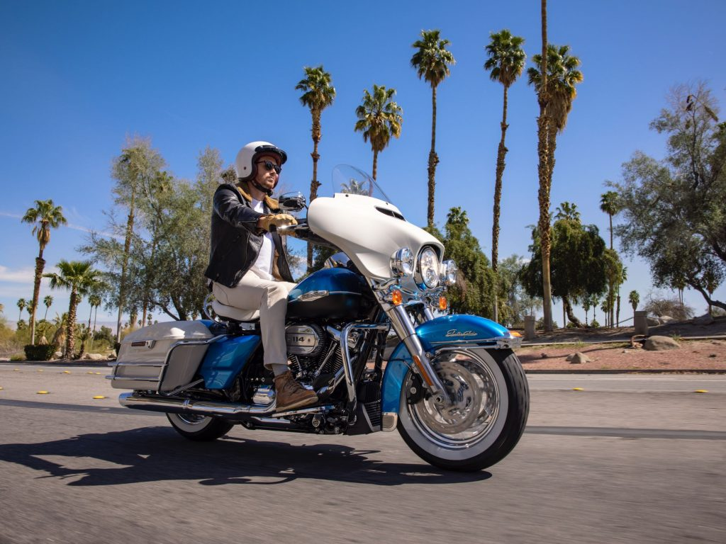 A rider takes a blue-and-white 2021 Harley-Davidson Electra Glide Revival down a palm-tree-lined street