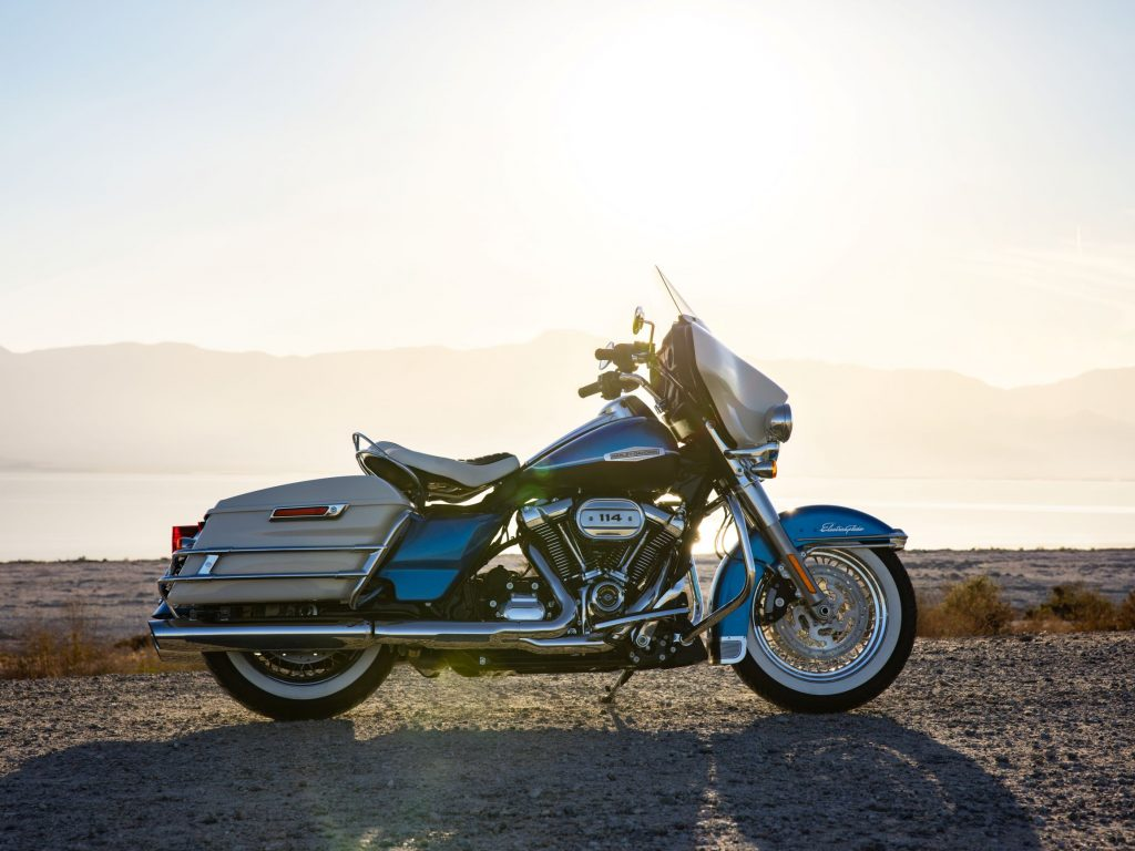 The side view of a blue-and-white 2021 Harley-Davidson Electra Glide Revival on a rocky beach